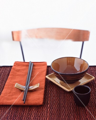 A place laid at a table with an oriental bowl and chopsticks on a chopstick rest