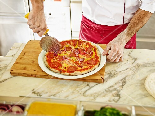 A chef cutting a pizza into portions using a pizza wheel
