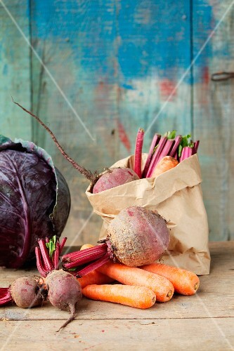 Rustic still life of vegetables, featuring carrots, beetroot and red cabbage