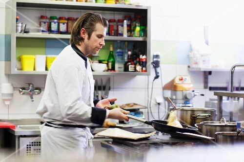 A chef preparing a dish in a frying pan