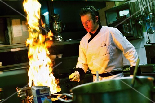 A chef with a flaming pan in a restaurant kitchen
