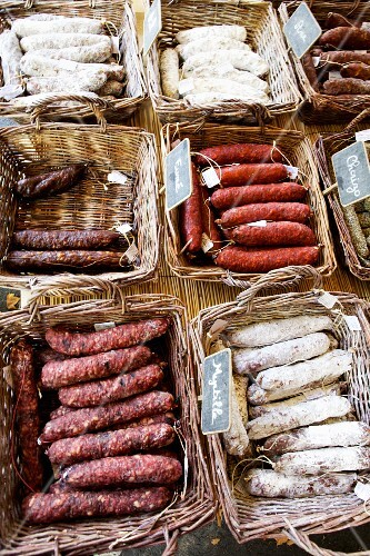 Assorted smoked sausages in baskets at the market