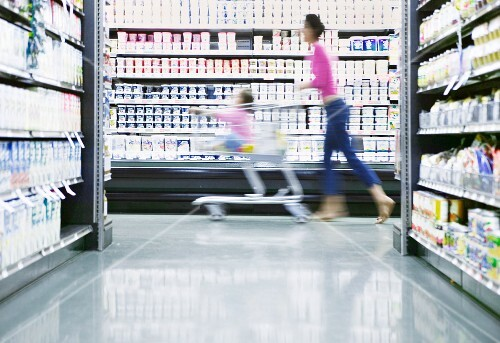 A mother pushing her daughter around the supermarket in a shopping trolley