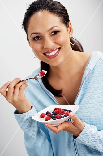 Portrait of woman eating bowl of fruit