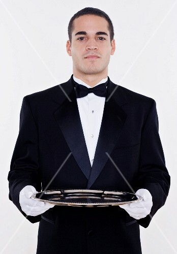 Portrait of male waiter holding tray