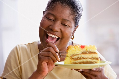 Middle-aged African woman about to eat a piece of cake