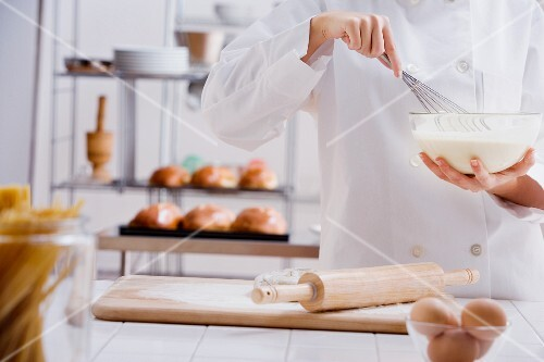 Female pastry chef whisking batter