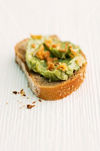A slice of bread topped with herb spread