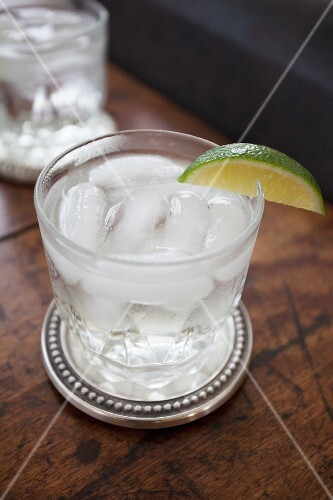 A glass of gin and tonic with ice cubes and a slice of lime