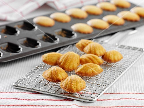 Madeleines in a baking tray and on a wire rack