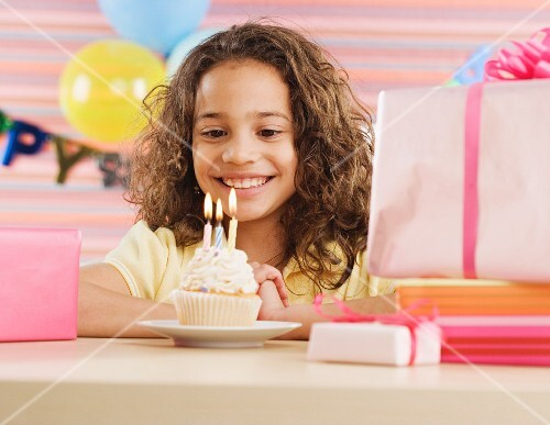 Young girl with cupcake and lit candles at birthday party
