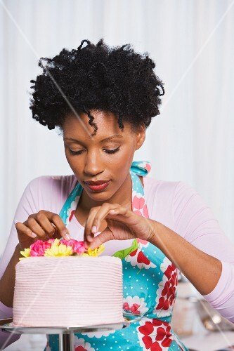 Young African woman putting flowers on cake