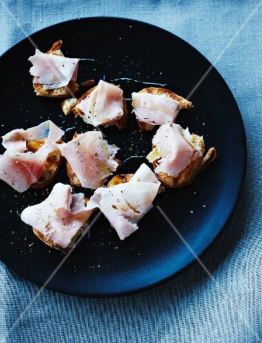 Toasted chunks of bread with ham and olive oil