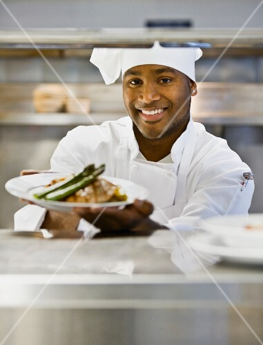 African male chef holding plate of food