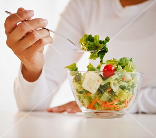 Mixed race woman eating salad