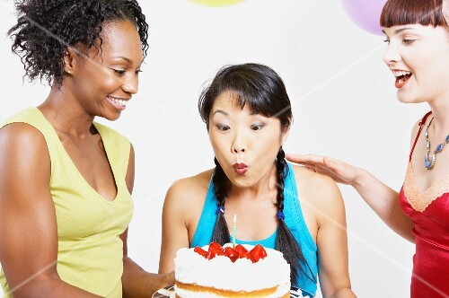 Asian woman blowing out candle on cake