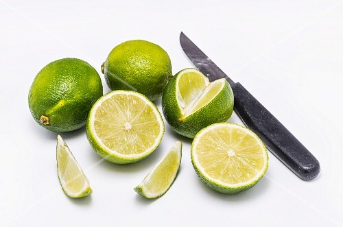 Fresh limes and knife in white background