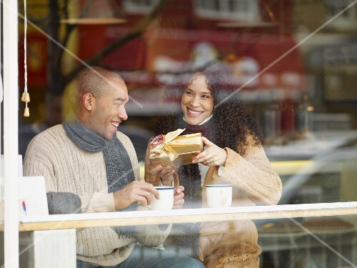 African woman giving boyfriend Christmas present in cafe