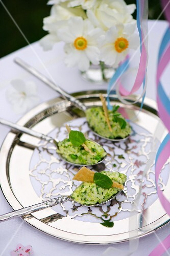 Spoon canapes with pea risotto on a silver tray for a baptism party