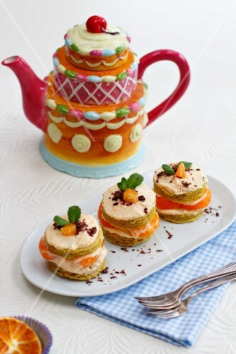 Individual mandarin layer cakes with quark cream icing, in front of a teapot