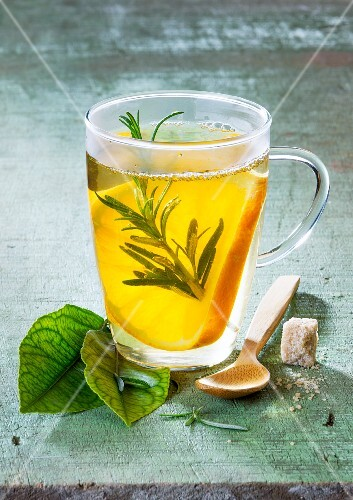 Orange tea with rosemary in a glass cup