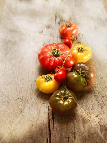 Assorted varieties of tomato (Noire de Crimee, oxheart and pineapple tomatoes) on a wooden surface