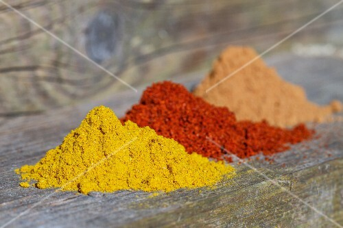 Three mounds of different spices