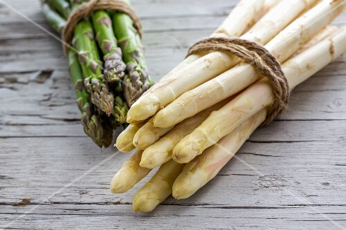 Green and white asparagus, tied in bundles, on a wooden surface