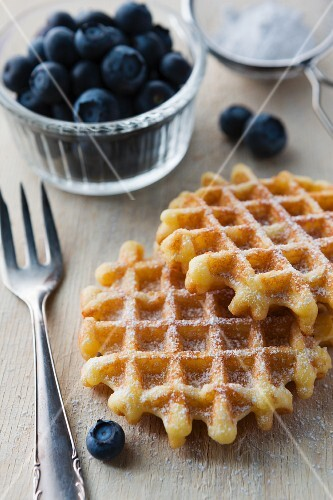 Waffles with icing sugar and fresh blueberries