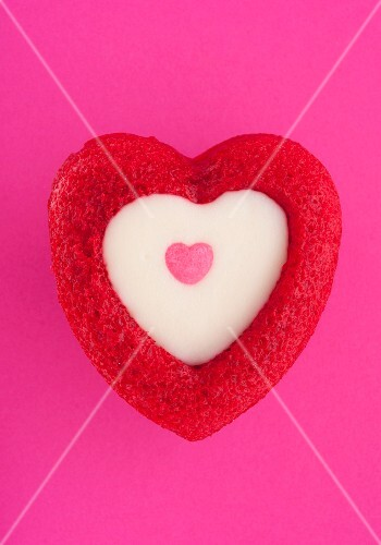 Heart-shaped muffin with white chocolate topping on pink background