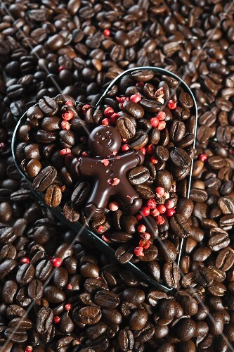 A chocolate figure on top of coffee beans with red peppercorns in a heart-shaped cutter