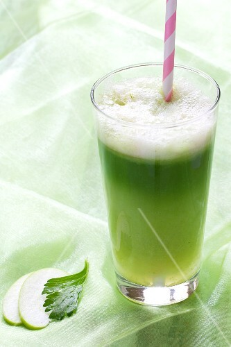 Green vitamin juice in a glass with a straw