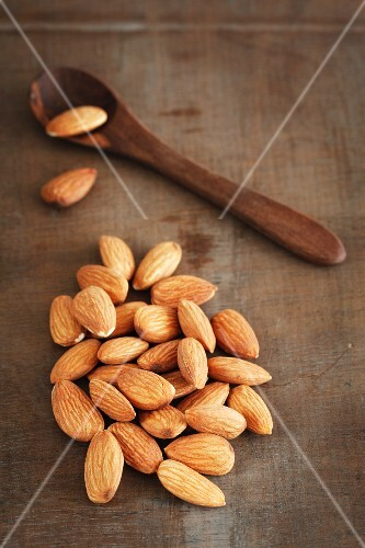 Almonds on a wooden surface with a wooden spoon