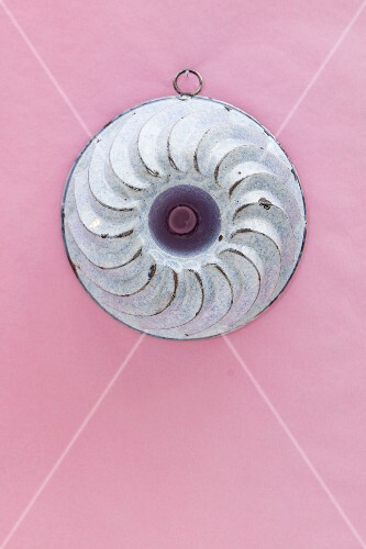 An old Bundt cake mould hanging on a pink wall