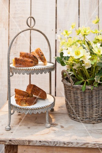 Slices of Bundt cake on a cake stand next to a basket of spring flowers