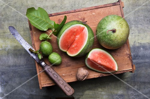 A sliced water melon, walnuts and a knife on a wooden board