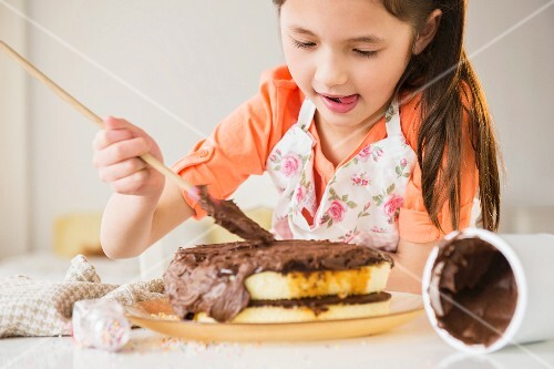 A girl spreading chocolate cream onto a cake