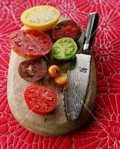 Various halved tomatoes on a wooden board