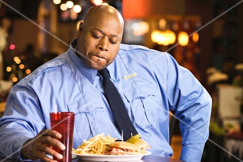 A dark-skinned, overweight policeman eating fast food