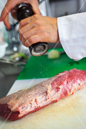 preparation of a typical Czech dish called Svickova, seasoning a tenderloin beef with pepper and salt