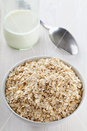 A bowl of oats in front of a bottle of milk