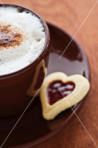 A cappuccino and a jam biscuit