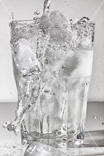 Water being poured into a glass of ice cubes