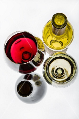 A glass of red wine, a glass of white wine and wine bottles