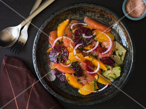 Citrus salad with grapefruit, orange, lime, mint and red onions in a dark stoneware plate with silver utensils on a dark surface