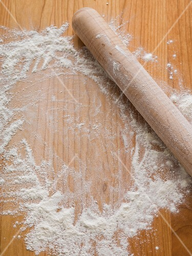 Flour sprinkled on a wood surface woth a rolling pin