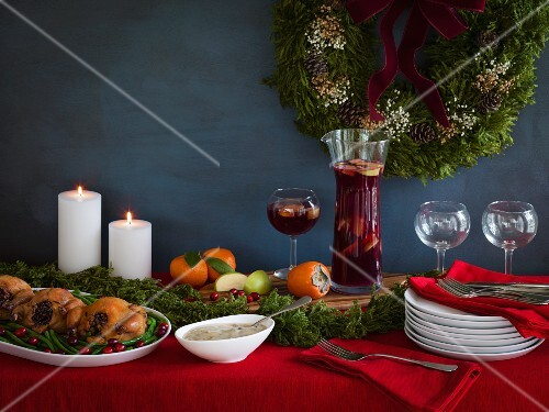 Holiday meal ready for serving with cornish game hens on a bed of green beans and cranberries, gravy and red sangria with stacked plates on a red tablecloth with white candles and a wreath in the background