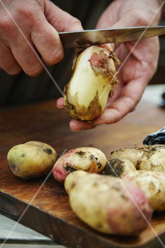 Potatoes being peeled on a chopping board