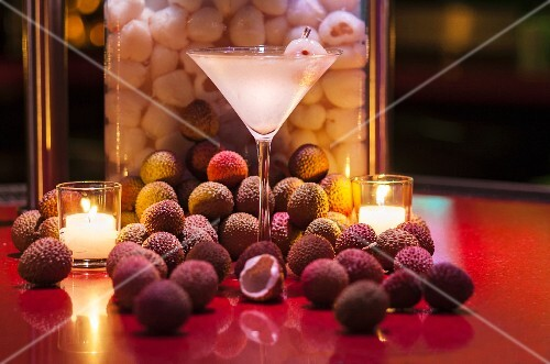 A lychee martini between tea lights and surrounded by fresh lychees