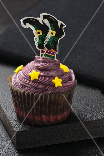 A chocolate cupcake decorated with a witch for Halloween